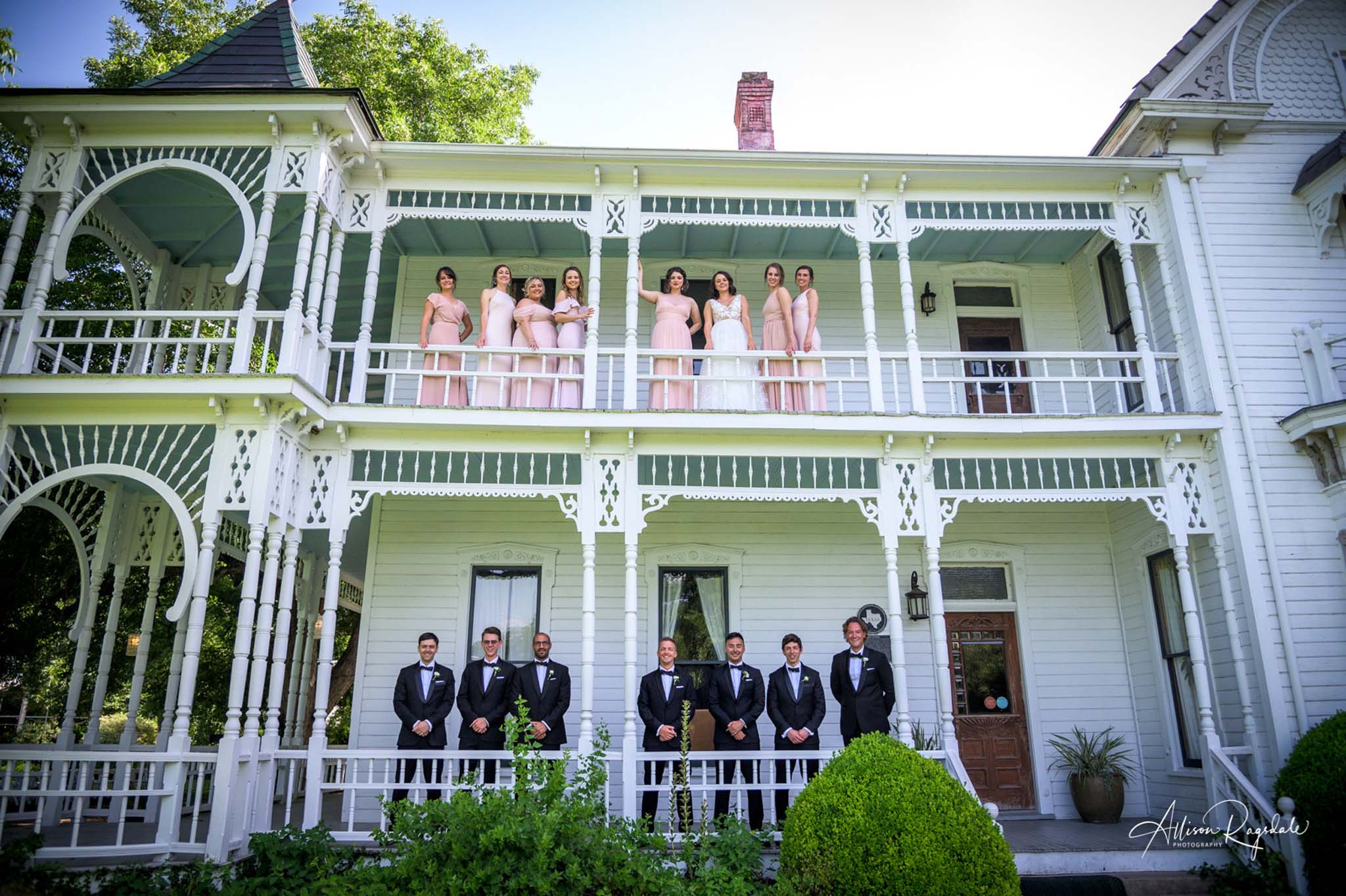 wedding party posing on two stories, bridesmaids on top balcony, groomsmen on bottom