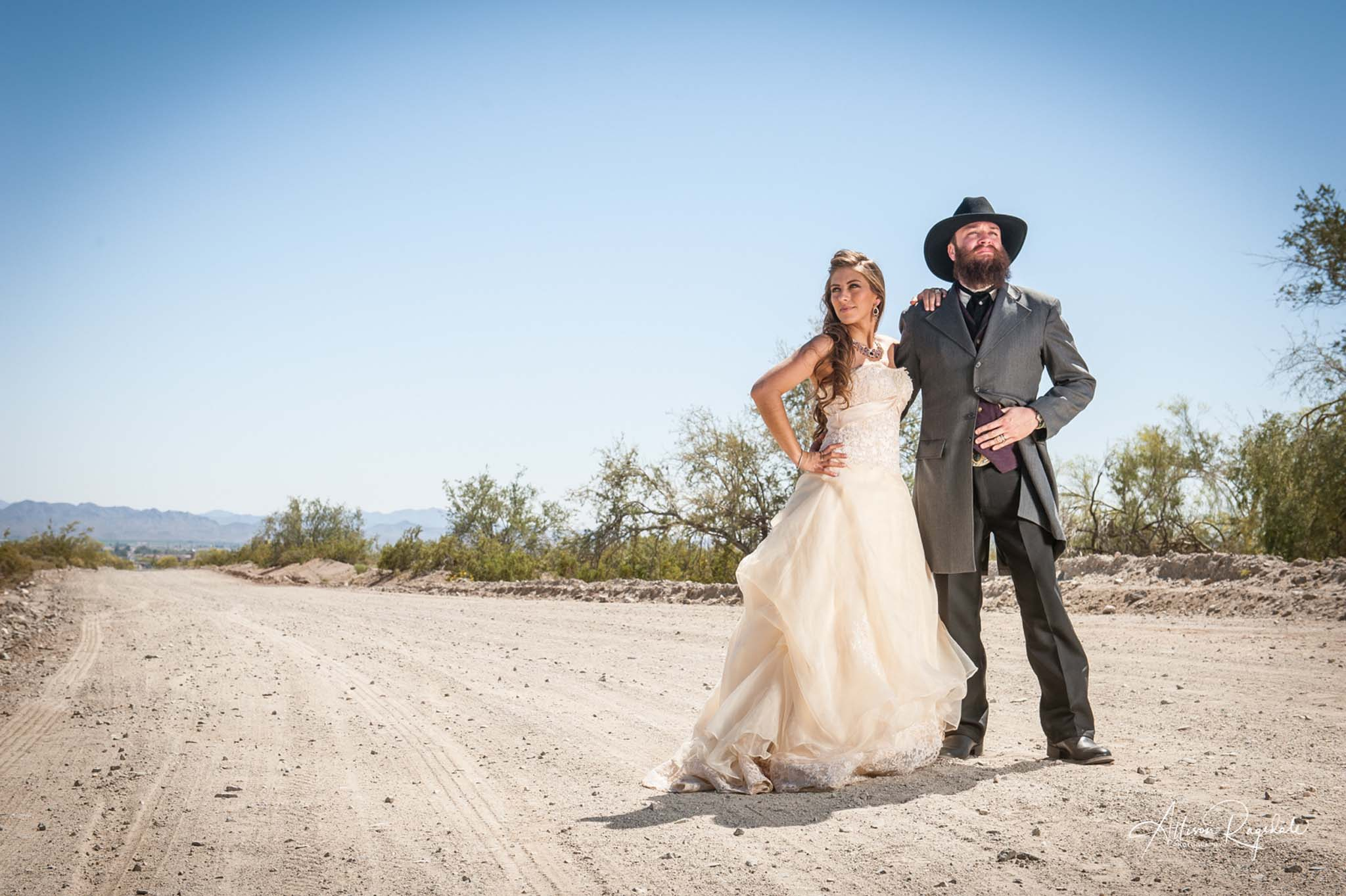 newlyweds posing on a dirt road