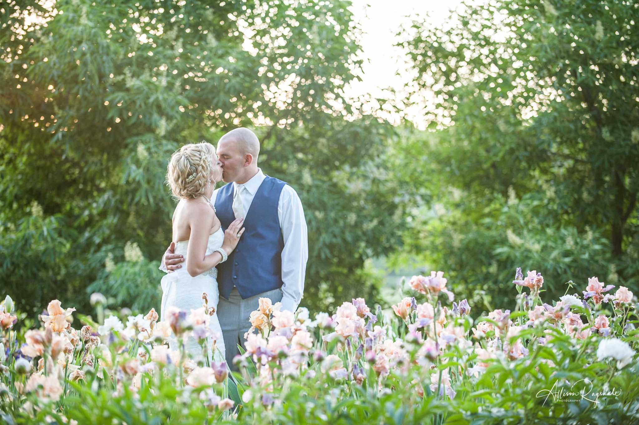 newlyweds embracing in a field of flowers