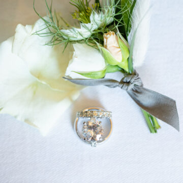 wedding bouquet and wedding rings close up. white roses. white gold